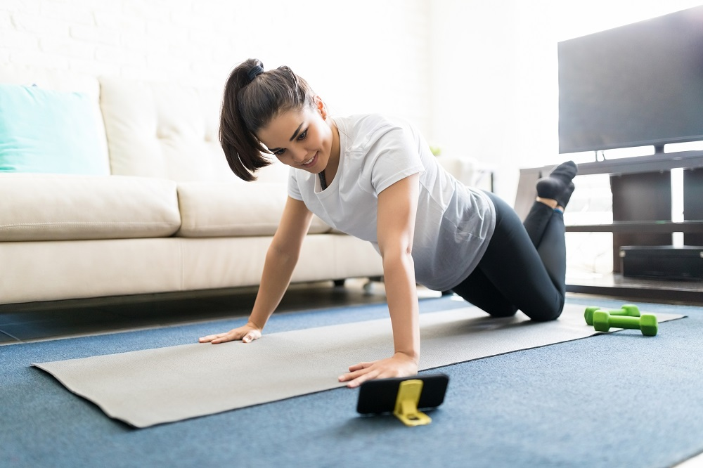 Woman doing a push up in her living room as part of a fitness class. It shows her achieving her financial resolutions for 2021, since she's getting fit and saving money on a gym membership.